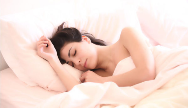 head and shoulders of woman sleeping on her side in pale pink sheets