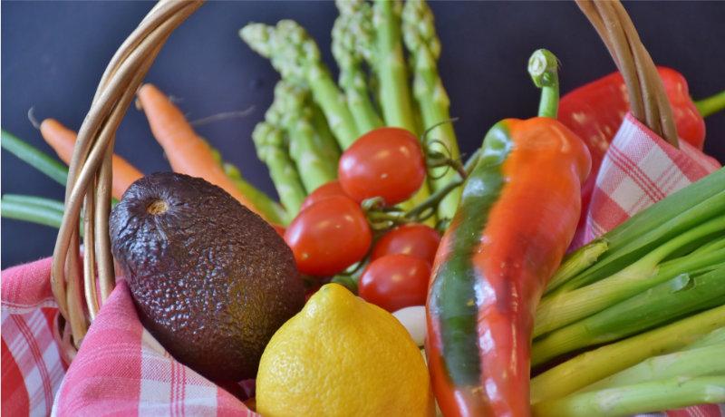 vegetables in a basket asparagus, tomatoes, avocado, pepper, lemon