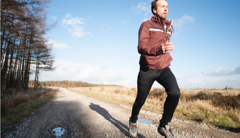 man running in sunshine with woods on his right and fields on his left, wearing maroon tracksuit top and black leggings