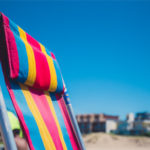 Top half of a deck chair with bright pink, blue and yellow stripes against a clear blue sky and some sand and buildings in the background but hazy